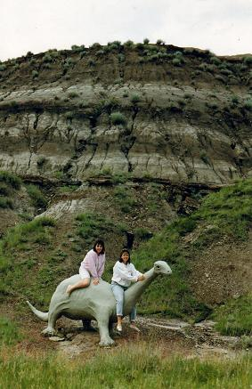 Tara and Lidia on top of  a small dinosaur