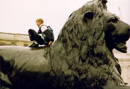 A child playing on top of a lion in Trafalger Square